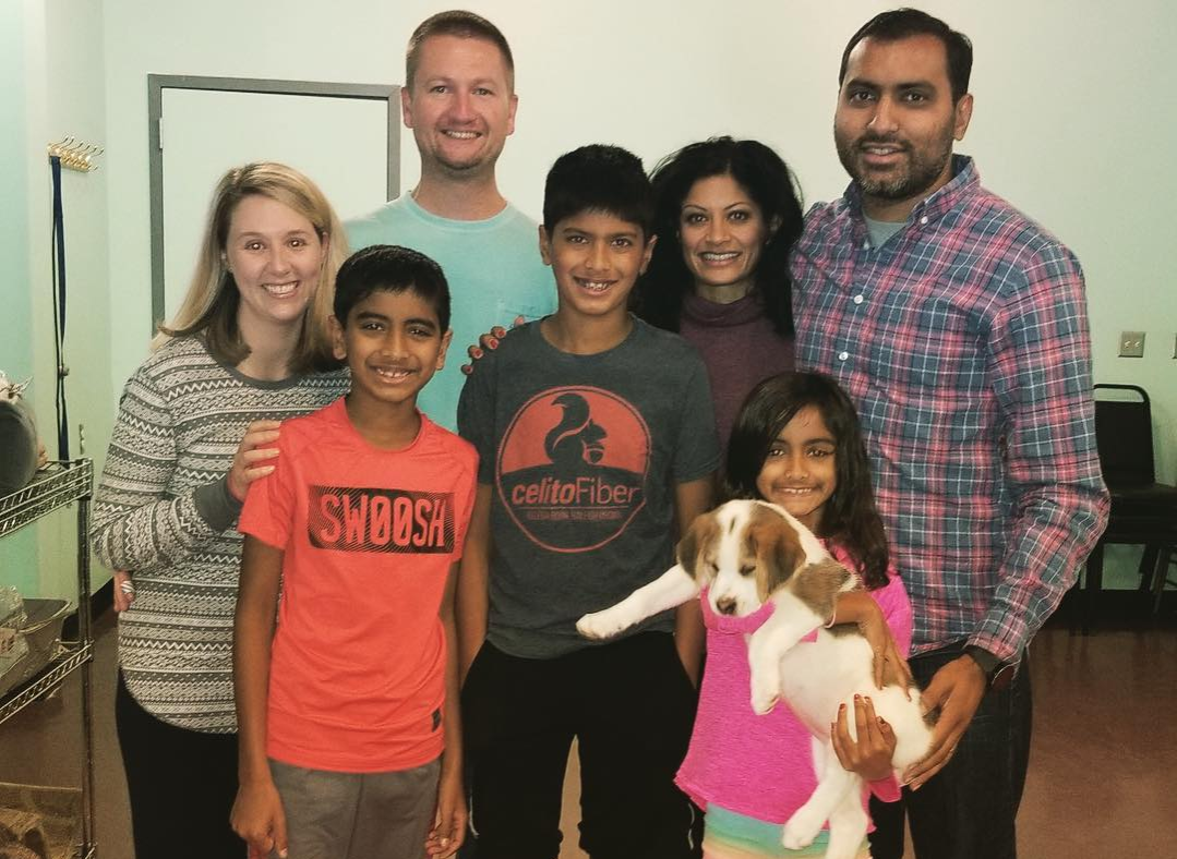 Kate and John smile with family who adopted one of Rosie's young puppies