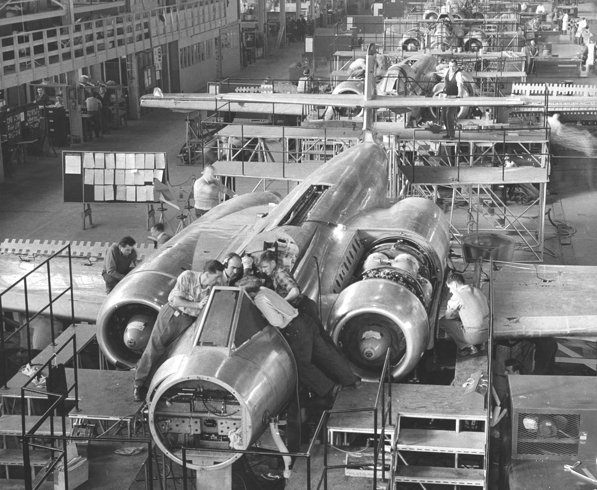 Men work on CF 100 jet fighter in an assembly line that fills the plant.