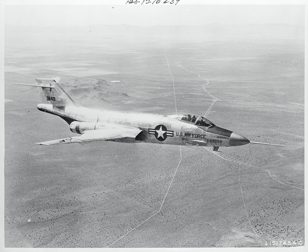 The McDonnell F-101 is captured in aerial view flying far above land.