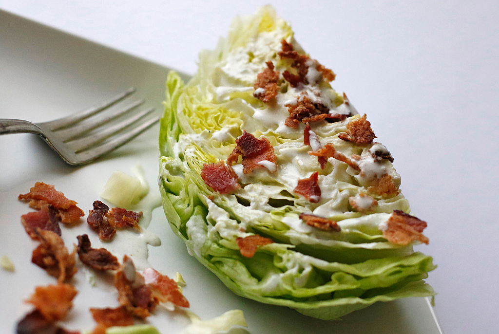 A simple wedge salad sits on a plate
