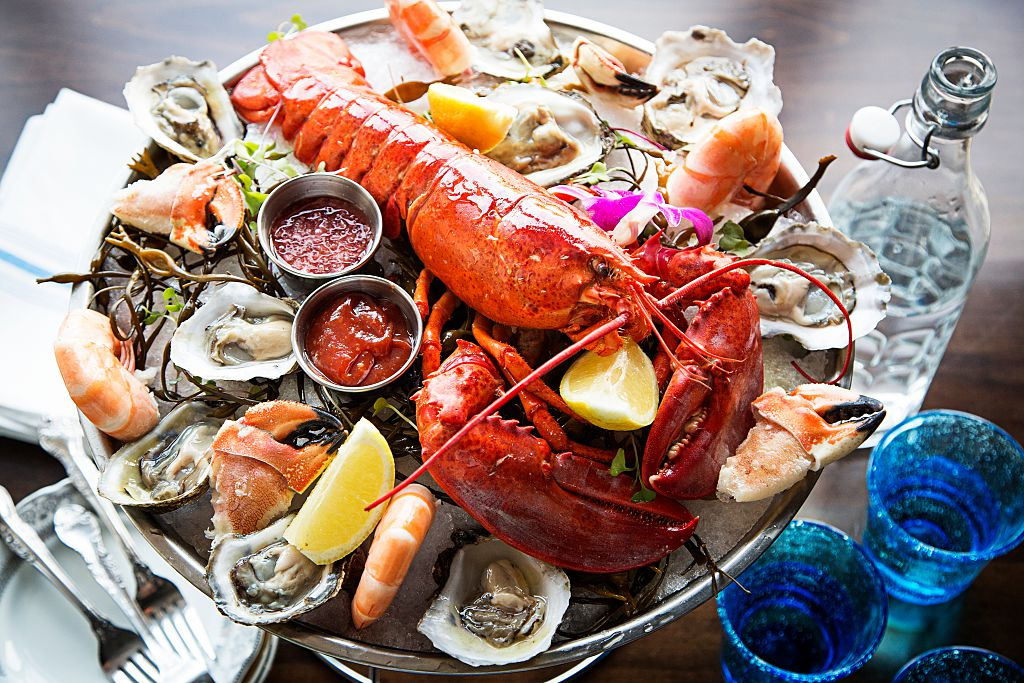 lobster on a platter with oysters, shrimp, and dipping sauces