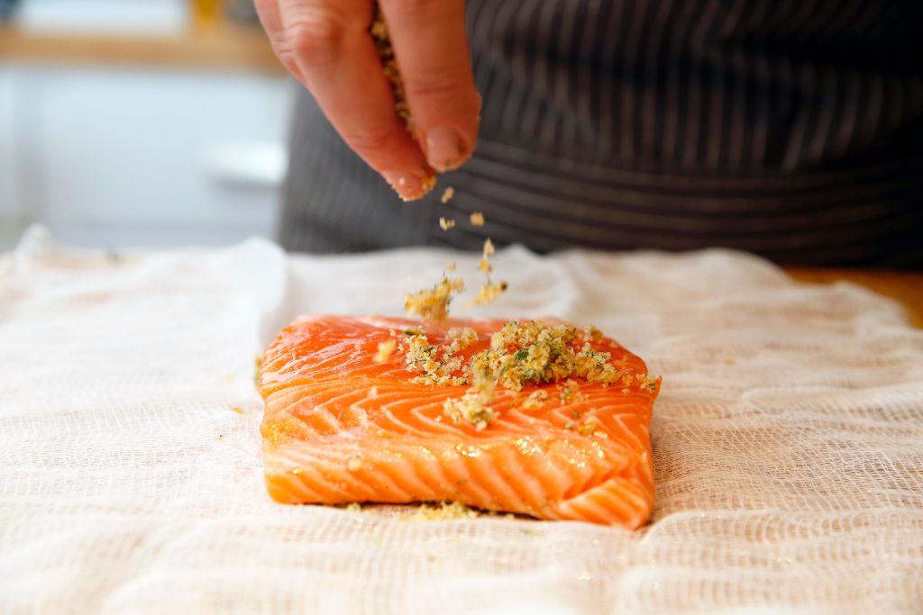 someone sprinkling a citrus rub on a salmon filet