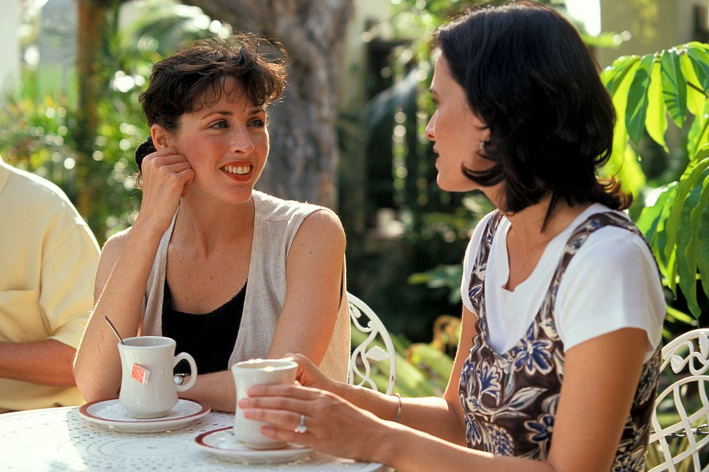 two women with tea at an outdoor cafe