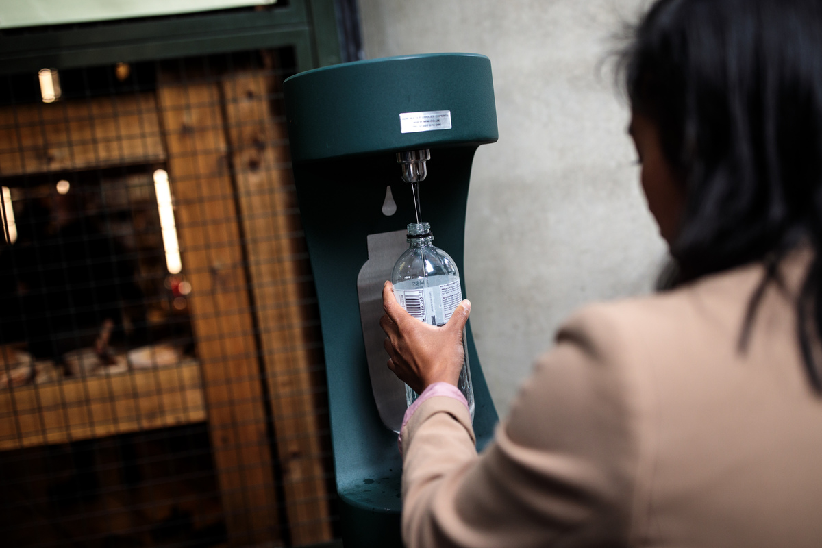 A woman refills a plastic bottle at a public water fountain.