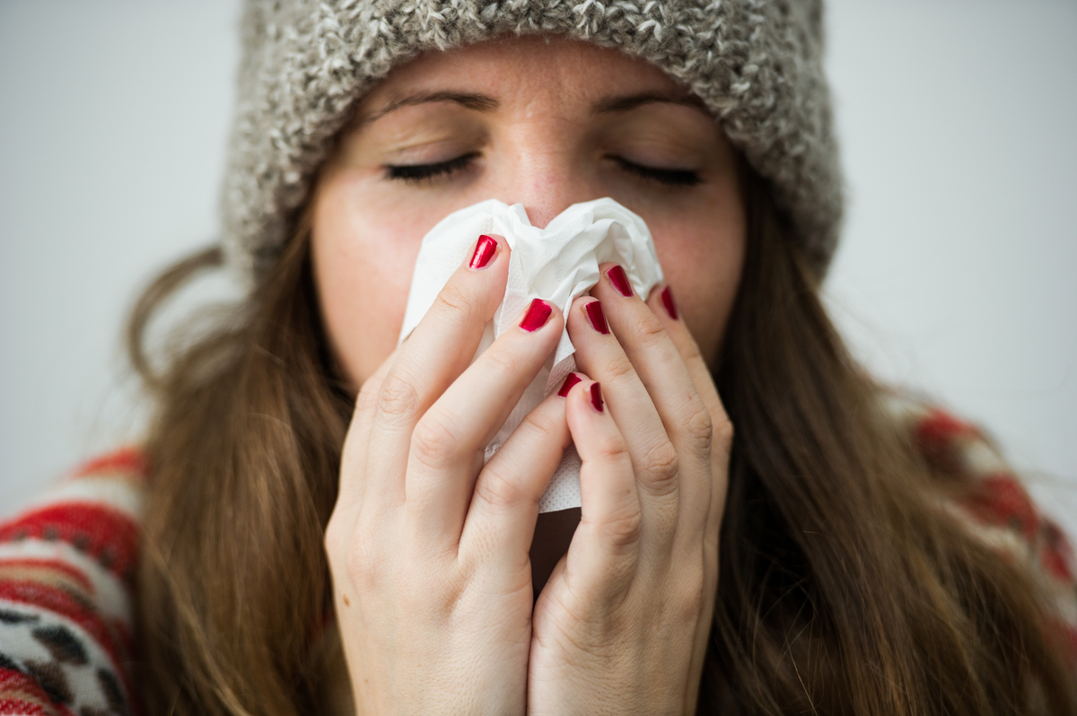 A young woman uses a tissue to blow her nose.