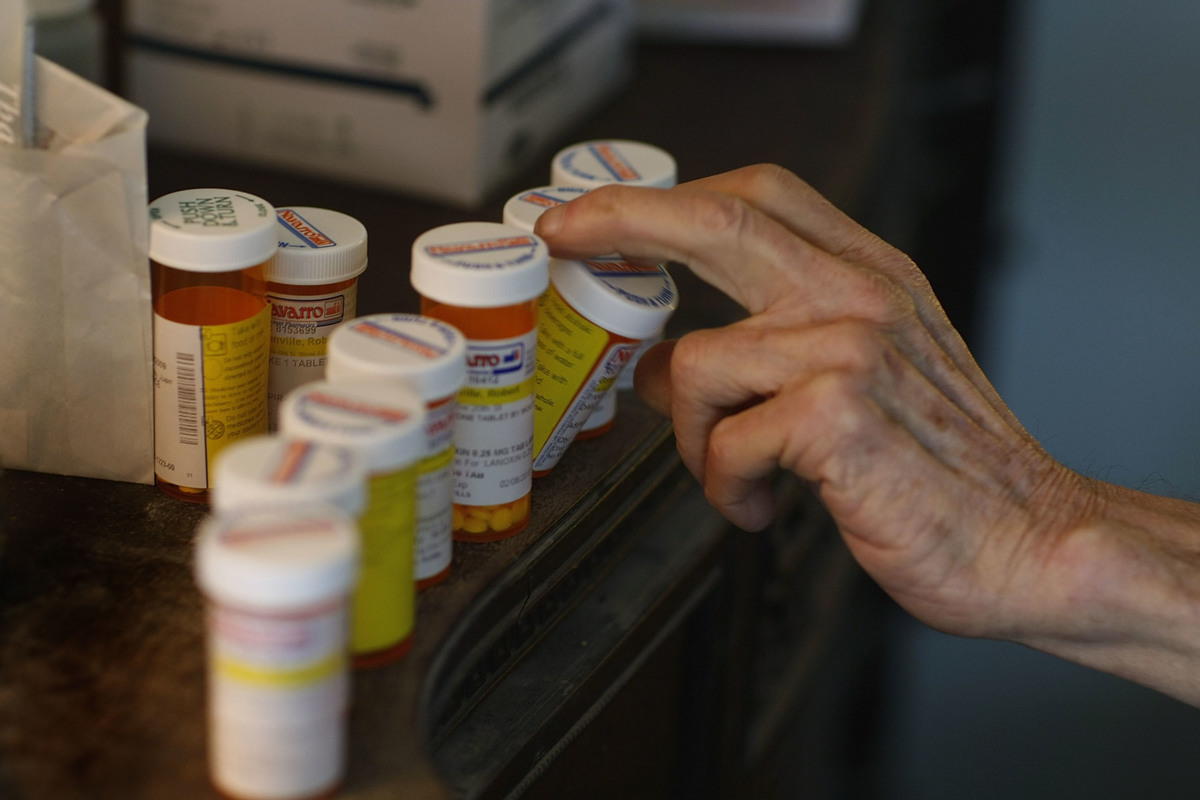 Robert Granville reaches for a medicine bottle as he takes his prescription pills.