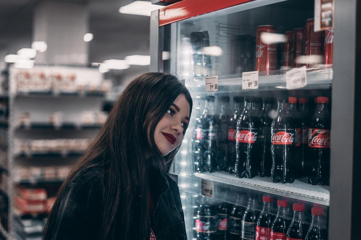 Woman looks at a fridge full of soda.