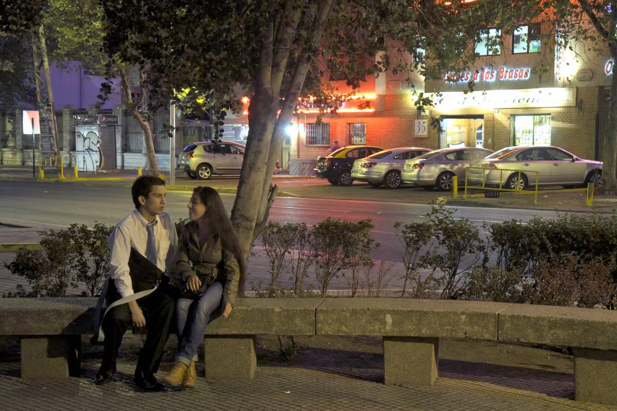 Couple sitting on a bench at night, Avenida Vicuna Mackenna.