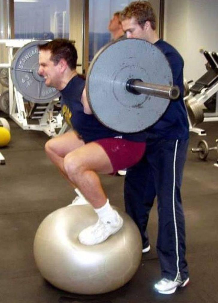 Homem em pé na bola de ioga enquanto levanta pesos