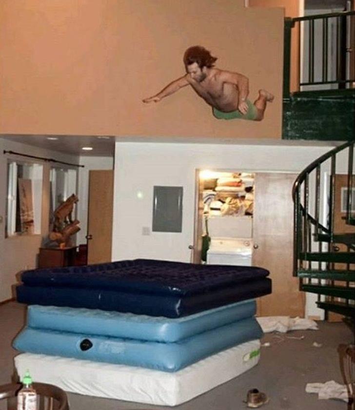 pessoa pulando da varanda na pilha de colchões infláveis