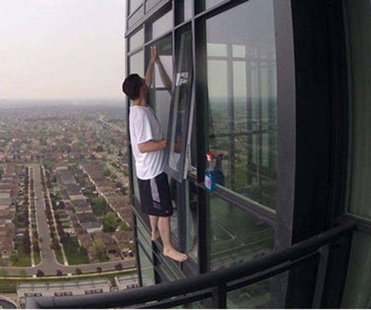 Person cleaning window on high rise building without any safety harness