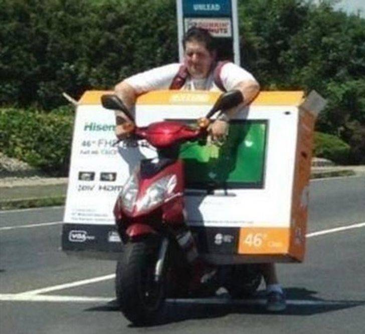 Person trying to transport oversized TV on a moped