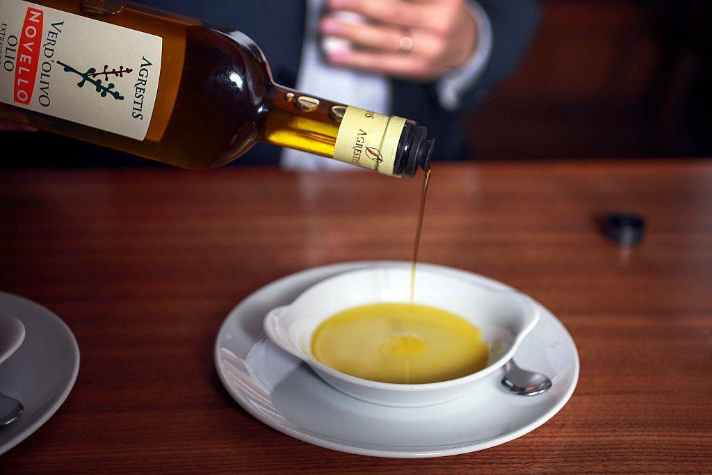 olive oil being poured into a bowl