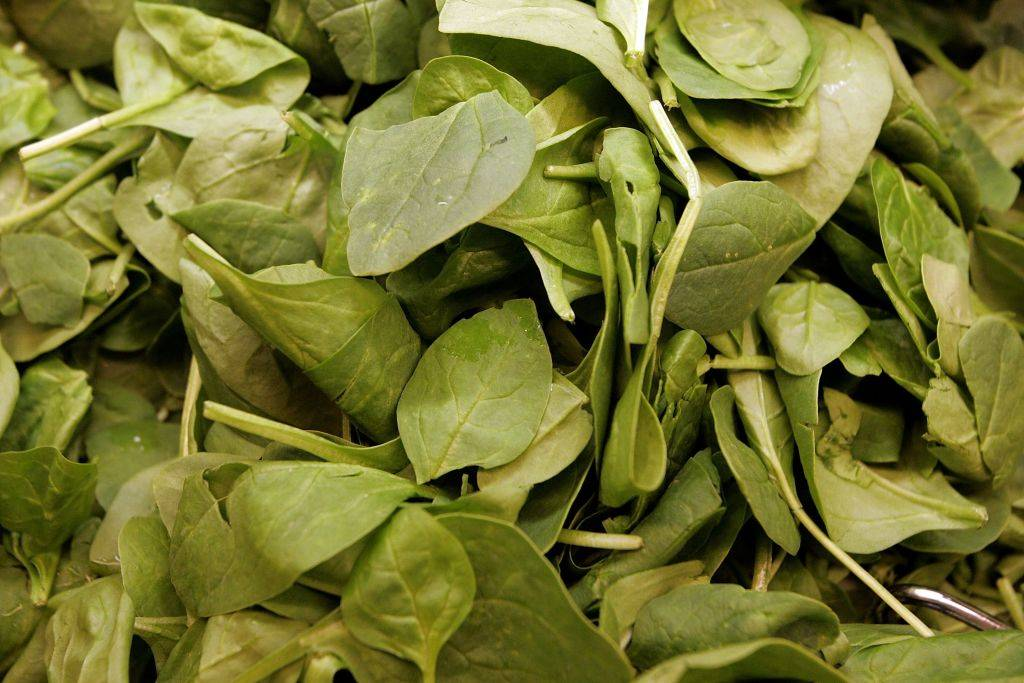 Fresh spinach leaves are seen in the produce section