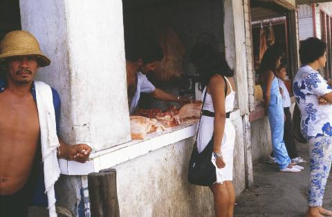 Woman orders meat from a local butcher in a market in Manaus, Brazil, December 1985
