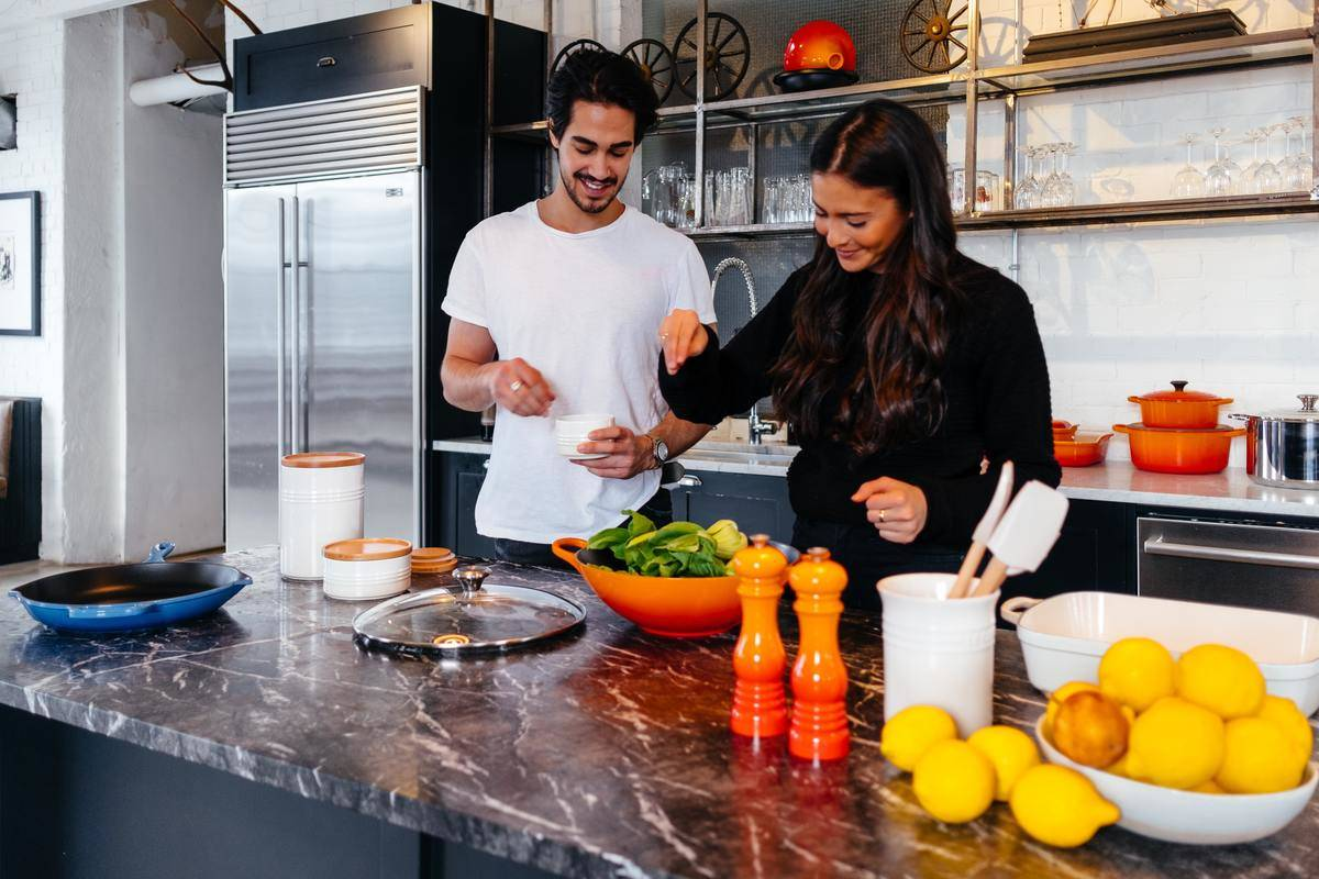 man and woman making a salad in the kitchen