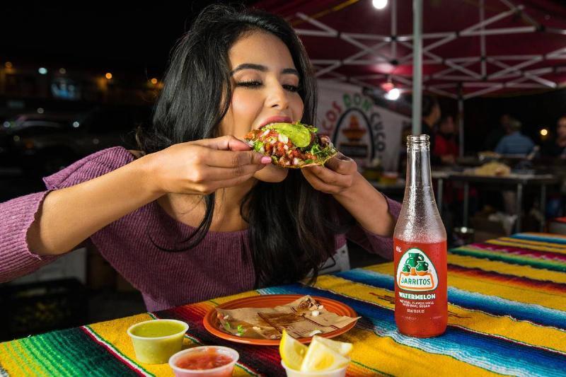 a woman eating a taco at night