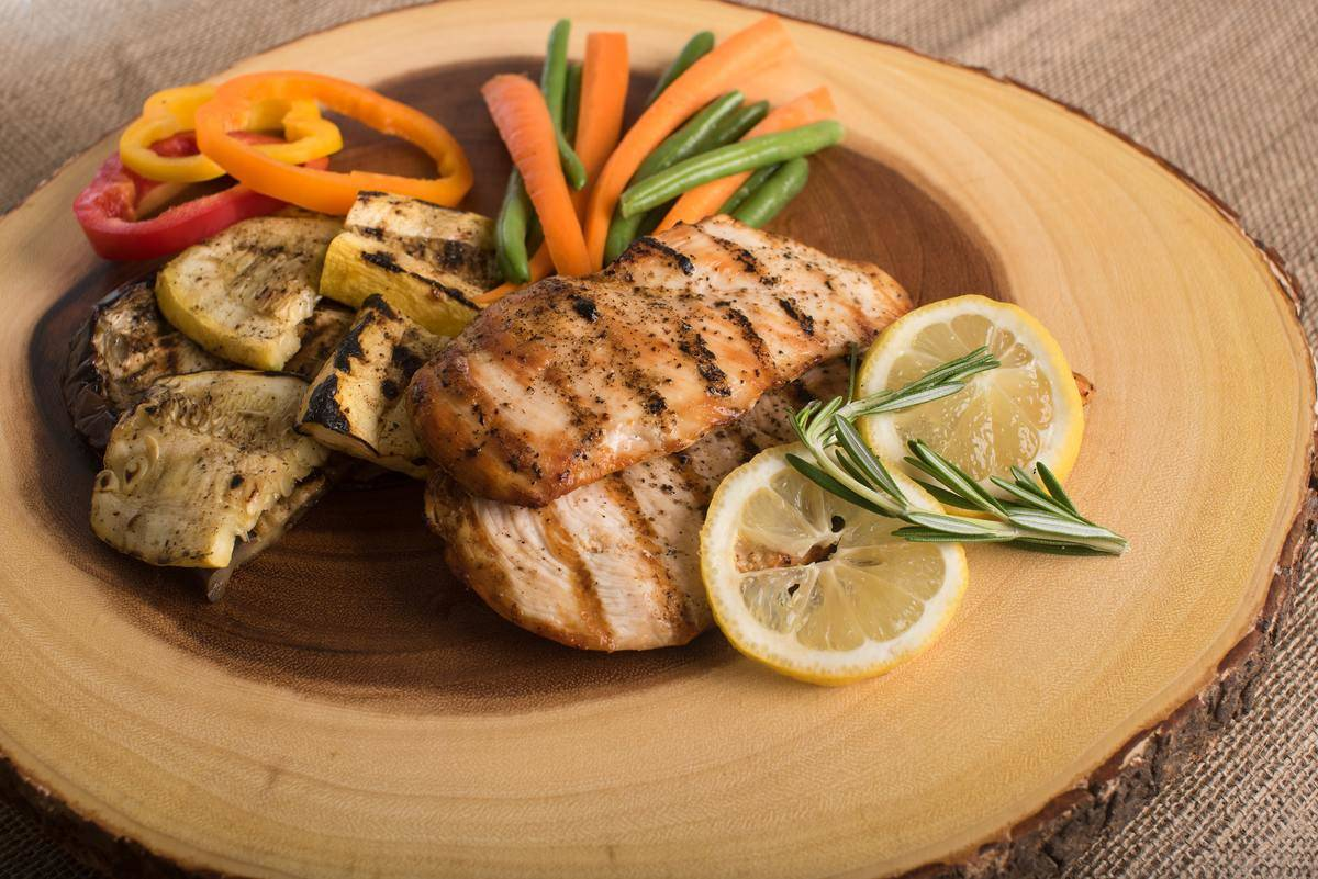grilled chicken, zucchini, peppers, green beans, carrots, lemons, and rosemary on a wooden plate