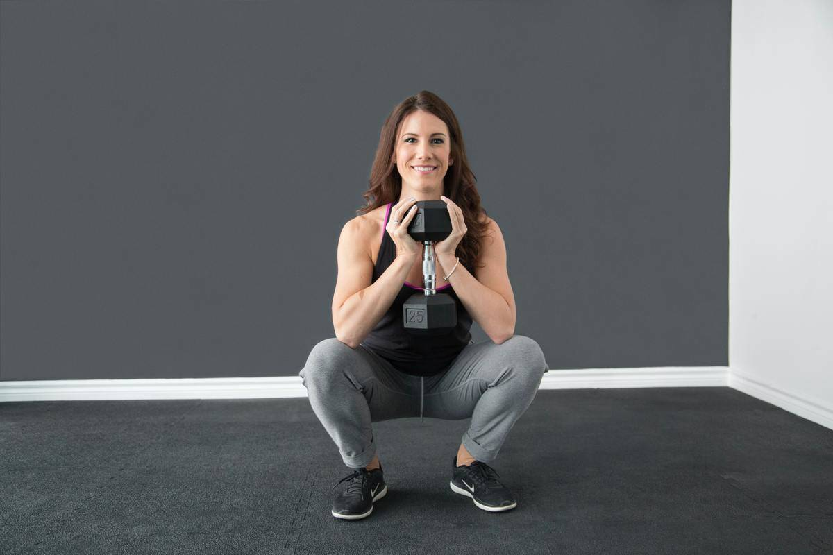 a woman squatting while holding a weight