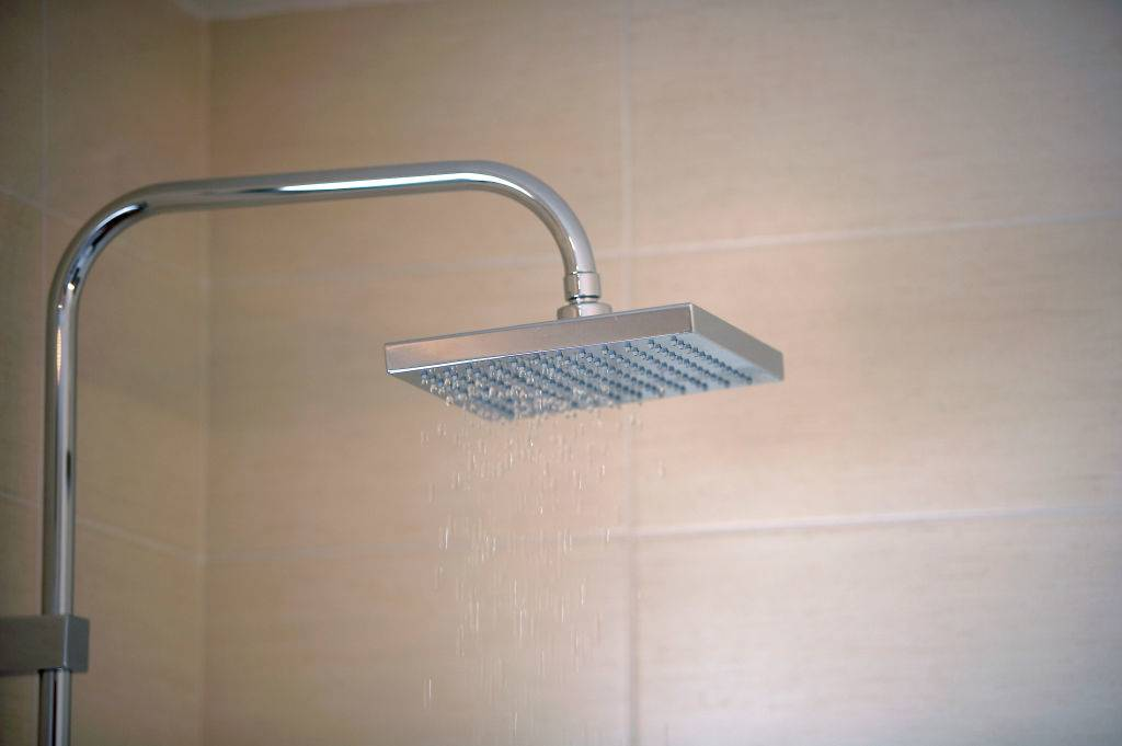 Close-up of a stainless steel shower with tiled wall