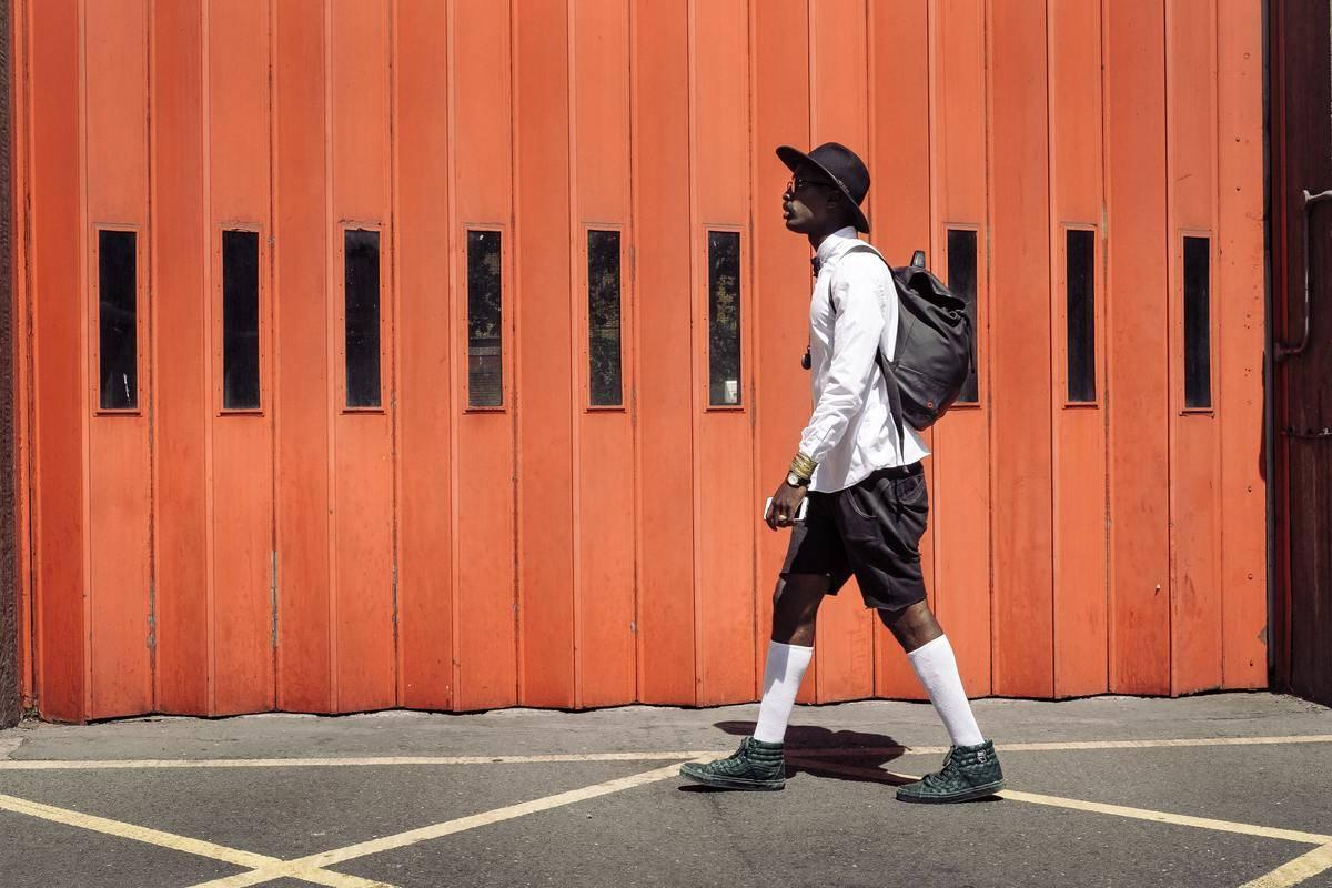 a man walking near an orange wall