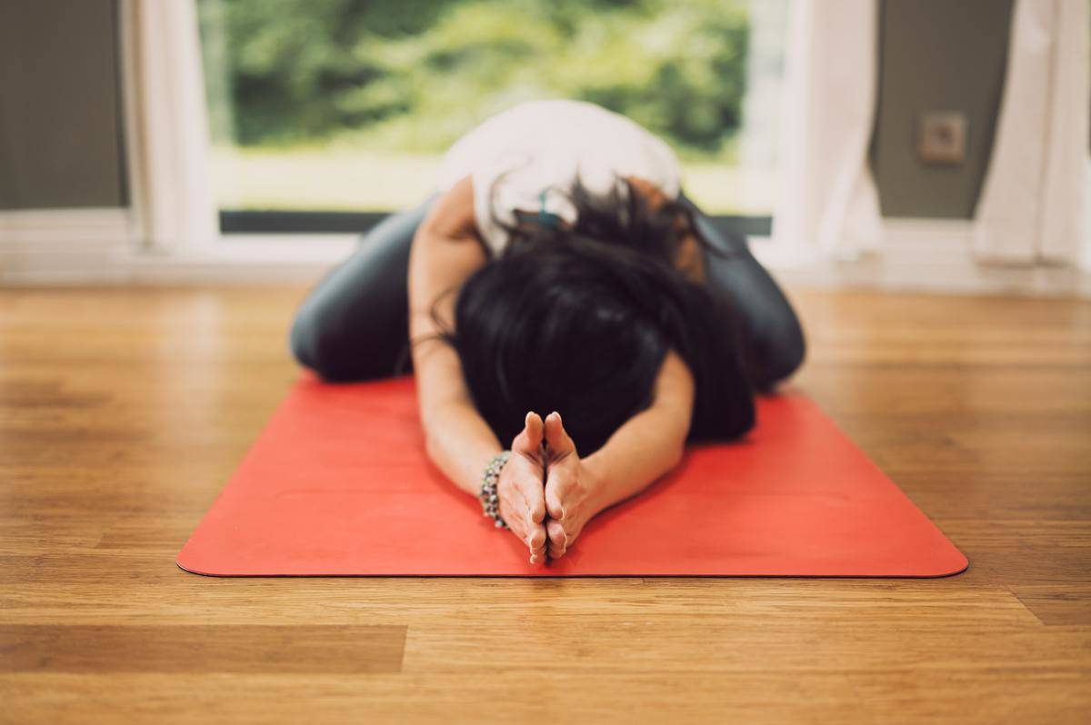 a girl with her face down and palms up doing yoga